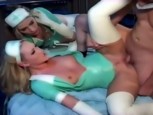 Two latex nurses in uniform have a hot threesome