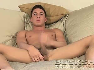 Young kinky guy masturbating on his bed after an interview