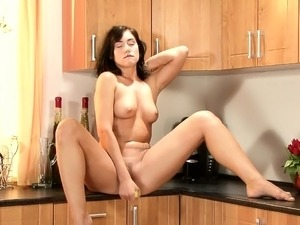 Slender nympho with a fabulous ass plays with a banana in the kitchen
