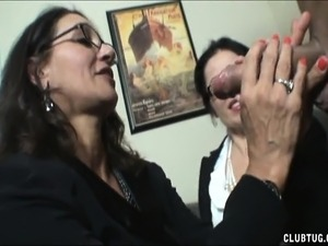 Two lustful ladies with glasses touch themselves and blow a big cock