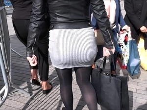 Voluptuous chick wears a gray skirt while showing her ass o